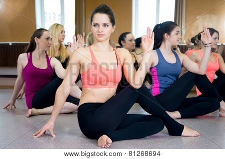 Group Of Yogi Females In Ardha Matsyendrasana Pose