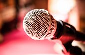 Close up of microphone in karaoke room or conference room.  red background (microphone, karaoke, music ) poster