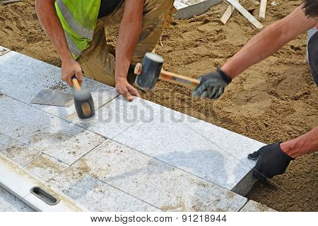 Workers Tapping Pavers Into Place With Rubber Mallets.