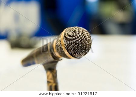 technology, electronics and audio equipment concept - close up of microphone at recording studio or radio station poster