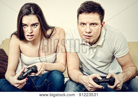 Couple Sitting In Living Room And Play Video Games On Console Or Pc With Joysticks