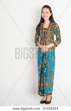 Full length Southeast Asian female in batik dress standing on plain background.