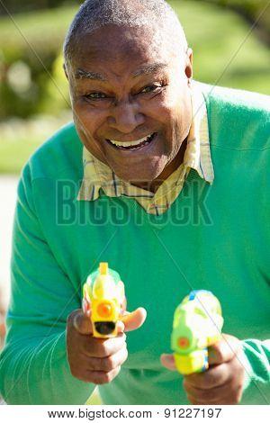 Senior Man Shooting Water Pistols