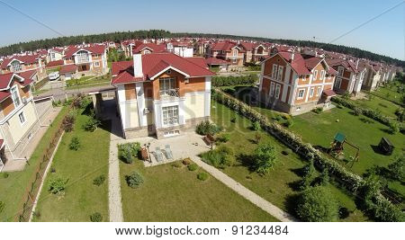 Aerial view many similar houses in gated development at sunny summer day.