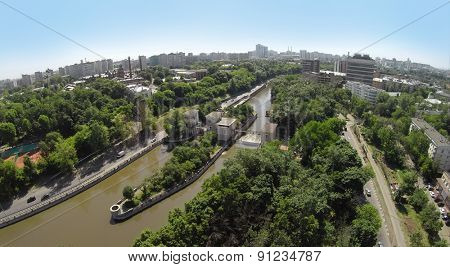 Cityscape with traffic on embankment of Yauza river with two sluices of Syromyatnicheskiy waterworks at summer sunny day. Aerial view