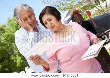 Worried Senior Hispanic Couple Checking Mailbox