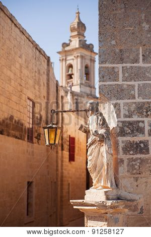 Ancient Narrow Street, The Carmelite Convent And Medieval Statue Of Jesus In The Old City Of Mdina.