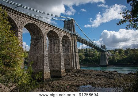 A view of the historic Menai suspension bridge spanning the Menai Straits Gwynnedd Wales UK. poster