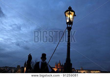 PRAGUE, CZECH REPUBLIC - DECEMBER 5, 2012: Lamplighter lights a street gas light manually during the Advent at the Charles Bridge in Prague, Czech Republic.