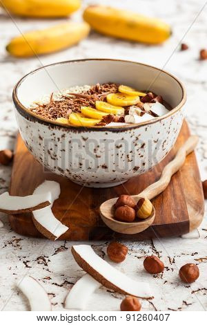 Chocolate hazelnut smoothie bowl topped with sliced banana, shredded coconut, chopped  chocolate, nuts and sesame seeds. Soft focus poster