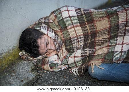 Young male beggar on city sidewalk sleeping