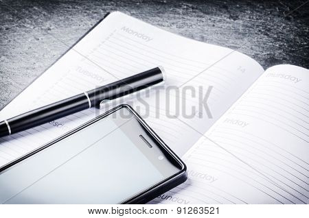 Business Concept With Agenda, Mobile Phone And Pen