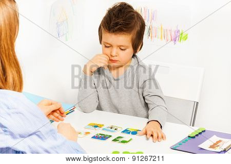Concentrated boy plays in developing game at the table with colorful cards with his parent indoors poster