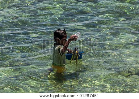 Sabah, Malaysia - September 11, 2011: Sea gypsy boy catches fish in the waters of the coral reefs around Mabul Island, Malaysia. Sea gypsies live all their live on the sea and make their living off it.