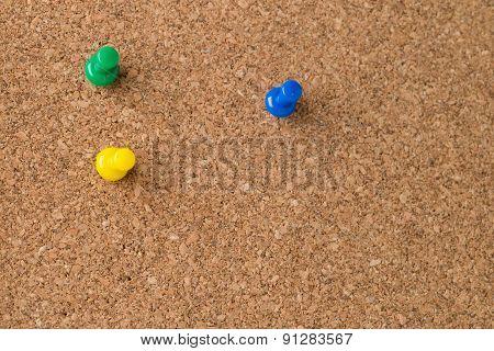 Three Colored Thumb Tacks On Cork Board