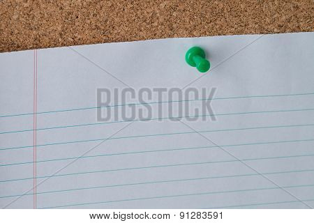 A green thumb tack holding a white piece of lined loose leaf paper on a cork board. poster