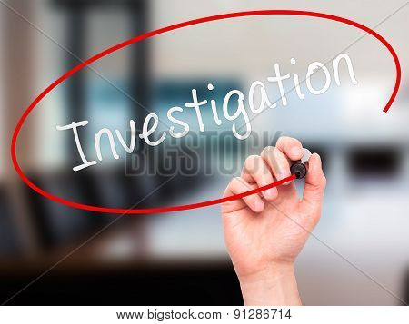 Man Hand writing Investigation with marker on transparent wipe board.