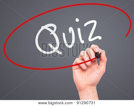 Man Hand writing Quiz with marker on transparent wipe board.