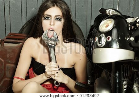 Sexy sensual young girl with gaudy make up in red dress holding and putting tongue into iron wrench in garage on workshop background horizontal picture poster