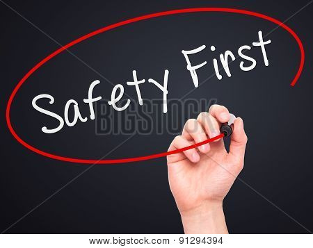 Man Hand writing Safety First with marker on transparent wipe board.