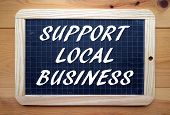 The phrase Support Local Business in white text on a slate blackboard poster