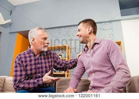 Close Up Portrait Of Aged Father Having Talk With His Adult Son