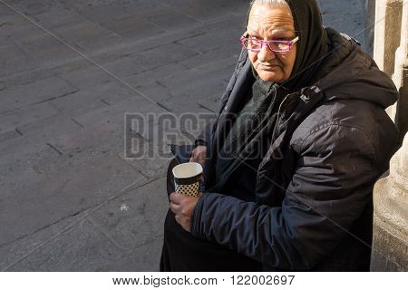 BARCELONA, SPAIN - JANUARY 21. An old Grandma is sitting in front of the church Santa Maria del Mar in Barcelona on January 21, 2016. Poor people in front of churches must beg for small money