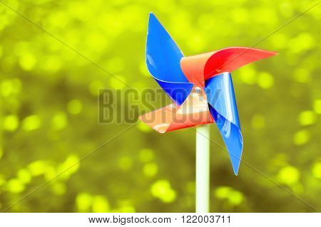 red and blue pinwheel. no wind conditions.motionless colorful pinwheel of four wings on a green blur background. copy space for your text