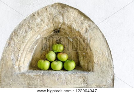 Apples piled in a triangle shap in a medieval alcove