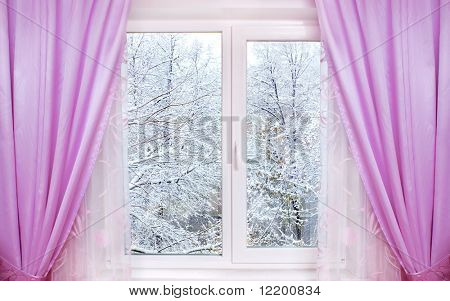 window with pink curtains and winter view behind it