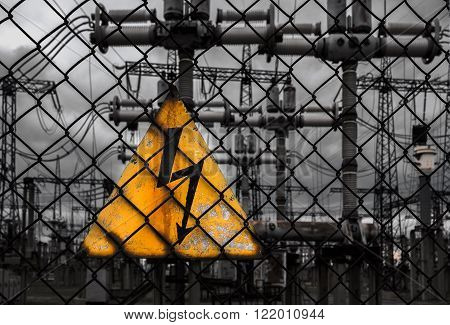 High voltage sign on a fence on a background of transformers and power lines. top view.