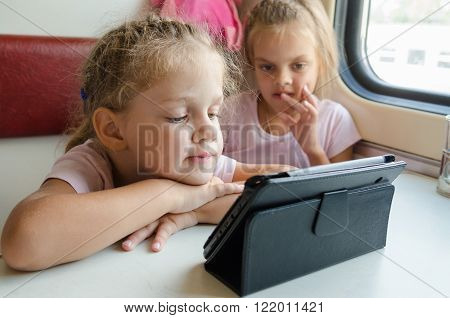 Two Girls On A Train With Interest Looking Cartoon Tablet Pc