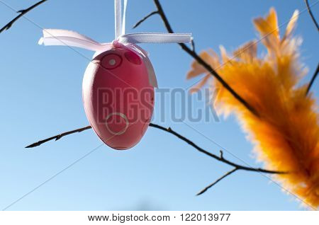 Pink egg hanging with orange feathers over a beautiful blue sky background.