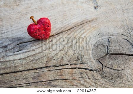 Wounded red heart shape pierced by rusty nail on a wooden board