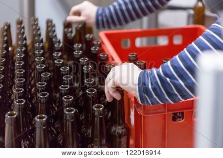 Close-up of unrecognizable man taking empty bottles and putting it in container on a craft beer elaboration process