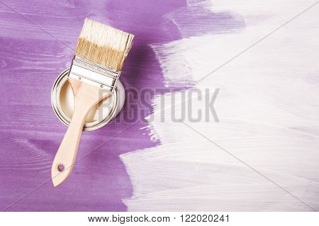 Paint brush on the can lying on violette wooden background. The surface is half - toned with white color. Top view.