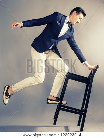 young handsoman businessman fooling aroung with chair, modern mem