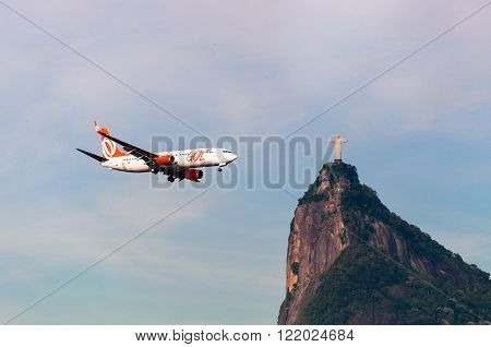 Rio de Janeiro, Brazil - February 26, 2016: Gol Airlines aircraft is flying towards the Christ the Redeemer statue on Corcovado mountain.