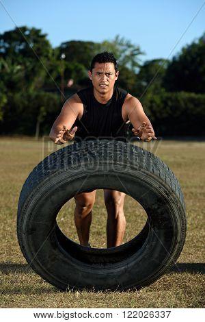 sportman flipping huge tire on grass stadium
