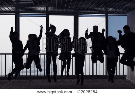 Group Of business people jump team silhouette. in front of the glass window