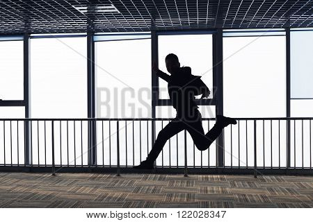 Men are jumping in the office corridor.Silhouette