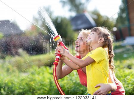 Portrait of little gardener girl with mother watering on lawn near house