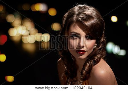 woman studio portrait in hollywood style light on black background with night lights city background