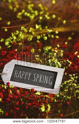 the text happy spring written in a label-shaped blackboard surrounded by many red and yellow small flowers