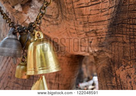 the gold bell hang on the chain under the elephant statue