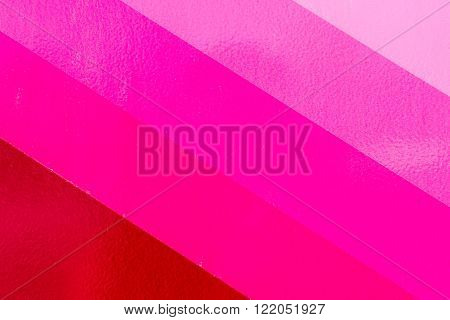 Varying shades of a pink color paint that covers a textured wall. Copy space diagonal areas with rough textures.