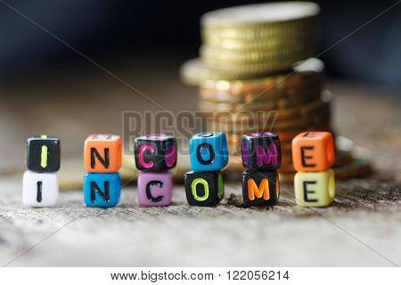 Close-up of colourful alphabet block with word INCOME. With pile of coins in the background.