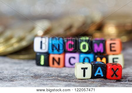 Close-up of colourful alphabet block with word INCOME TAX. With pile of coins in the background.