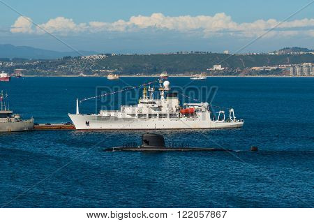 Valparaiso Chile - December 3 2012: Crew stands on deck of a Navy submarine as it returns to port Valparaiso and oceanographic survey US Naval ship Pathfinder Chile.