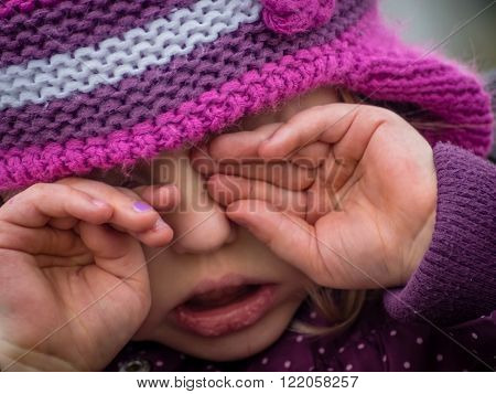 Little girl being very tired and sleepy and rubbing her eyes